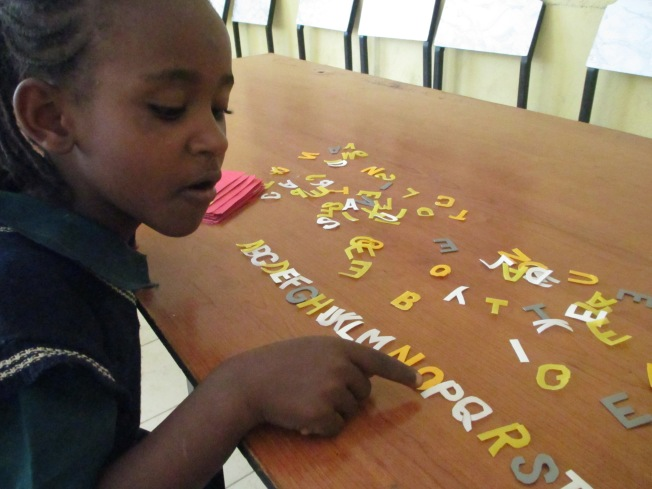 One of the orphans, learning her ABCs :)
